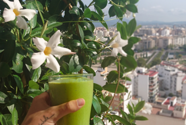 Mango Banana Spinach Smoothie with white flowers